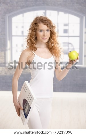 Attractive girl holding apple and scale in hands, living healthy.? - stock photo