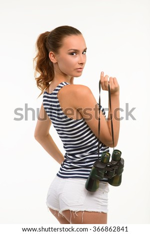 Attractive girl holding binocular. Side view of pretty sailor on white background. Picture of nice girl with mysterious look. - stock photo
