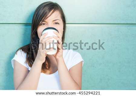Attractive girl holding coffee and drinking and enjoying outside on green wall with copy text space - stock photo