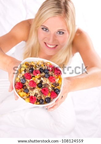 Attractive girl holding healthy bowl of cereals. Shot from upper view. Focus on bowl