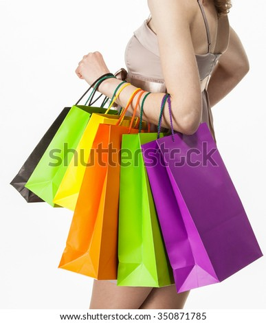 Attractive girl holding multicolored shopping paper bags - closeup shot isola