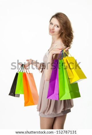 Attractive girl holding multicolored shopping paper bags - closeup shot on white background