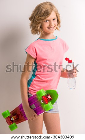 Attractive girl holding skateboard and bottle of water against white background. - stock photo