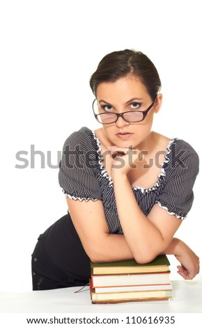 attractive girl in a blouse and glasses stands leaning on a pile of books isolated on white background
