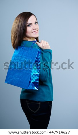 attractive girl in a blue t-shirt with a shopping bag on her shoulder, turned back .On a gray background