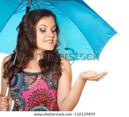 attractive girl in a bright dress holds in her right hand a beautiful blue umbrella. Put your left hand under the imaginary rain isolated on a white background.