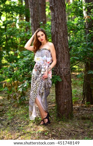 Attractive girl in a long dress posing in summer forest