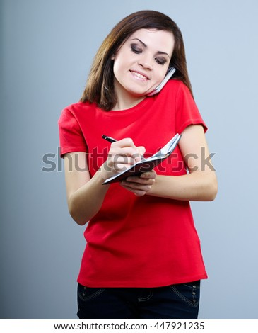 attractive girl in a red shirt talking on the phone and writes in a notebook on a gray background