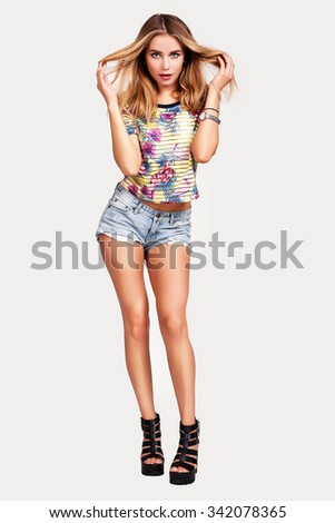 Attractive girl in a short jeans posing on white background. Beautiful suntanned sexy girl in short jeans shorts. - stock photo