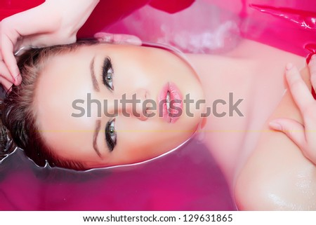 Attractive girl in bath with pink textile - stock photo