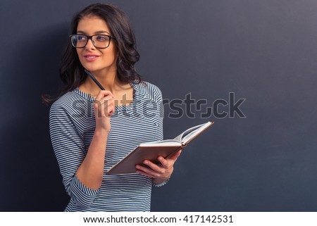 Attractive girl in casual clothes and eyeglasses is holding a notebook, looking away and thinking, standing against dark background - stock photo