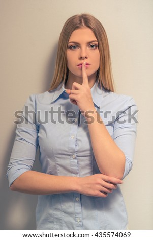 Attractive girl in classic clothes is keeping finger on lips showing silence sign and looking at camera, against gray background - stock photo