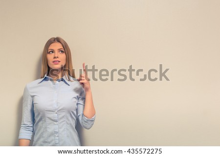 Attractive girl in classic clothes is pointing upward, looking away and smiling, against gray background - stock photo