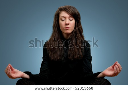 Attractive girl in dark clothes meditating, blue background - stock photo