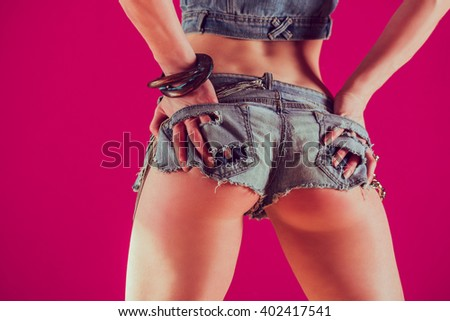Attractive girl in denim shorts on a pink background  - stock photo