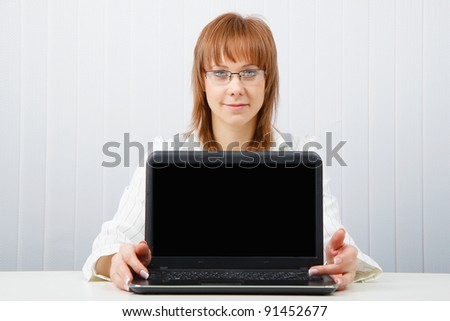 Attractive girl in glasses with a laptop in the office - stock photo