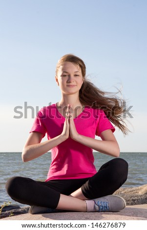 attractive girl in lotus pose sitting near sea - stock photo