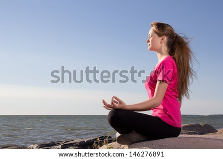 attractive girl in lotus pose sitting near sea