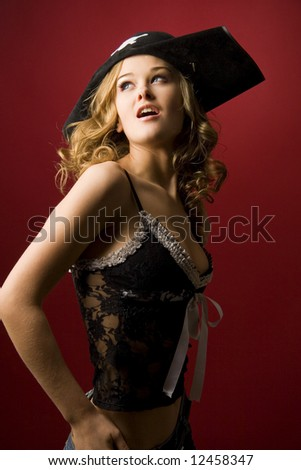 Attractive girl in pirate hat with skull isolated on red background - stock photo