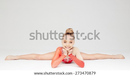 Attractive girl in red dress doing split. Isolated on white - stock photo