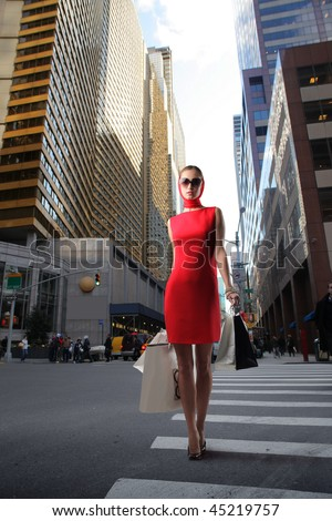 attractive girl in red dress with shopping bags crossing a city street - stock photo