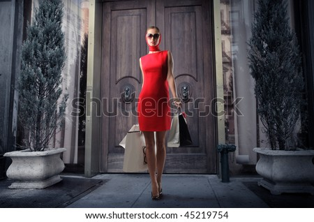 attractive girl in red dress with shopping bags outside a boutique - stock photo