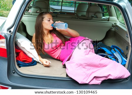 attractive girl in sleeping bag in her car drinks water - stock photo