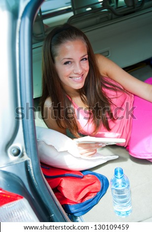 attractive girl in sleeping bag in her car on camping trip - stock photo