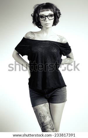 Attractive girl in spectacles alluring in sexual clothes. Beauty, fashion. Black-and-white photo. - stock photo