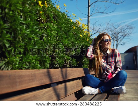 Attractive girl in sunglasses relaxing in the spring park while read book, female student sitting on wooden bench at campus, charming blonde hair young woman enjoying the sun at beautiful day outdoors - stock photo