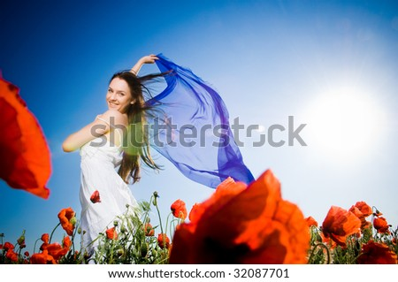 Attractive girl in the poppy field, low angle view - stock photo
