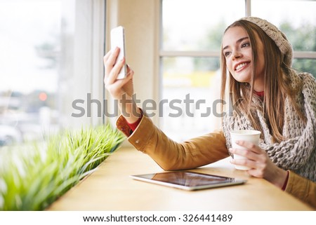 Attractive girl in warm clothes making selfie in cafe