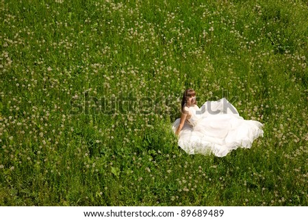 attractive girl in white dress sitting on meadow. outdoor shot