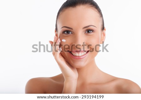 Attractive girl is applying cream on her cheek with pleasure. She is smiling happily. Isolated on white background and there is copy space in right side - stock photo
