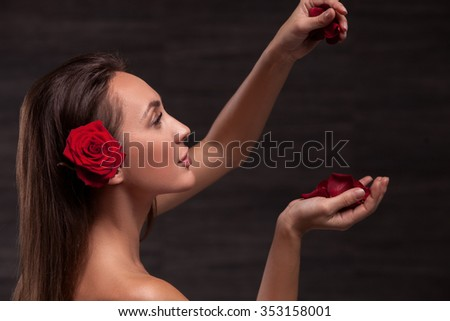 Attractive girl is carrying a red rose in her hair. She is holding petals and looking at it with passion. The lady is standing with naked shoulders - stock photo