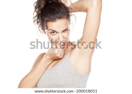 attractive girl is disgusted by her sweaty armpits - stock photo