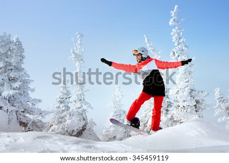 Attractive girl is having fun standing on snowboard in snowdrift on winter snowbound forest backdrop. Sheregesh resort, Siberia, Russia - stock photo