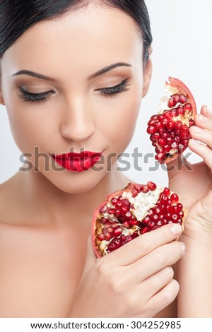 Attractive girl is holding slices of pomegranate in her hands. She is raising it to her face gently. The lady closed her eyes with pleasure. Isolated on background - stock photo