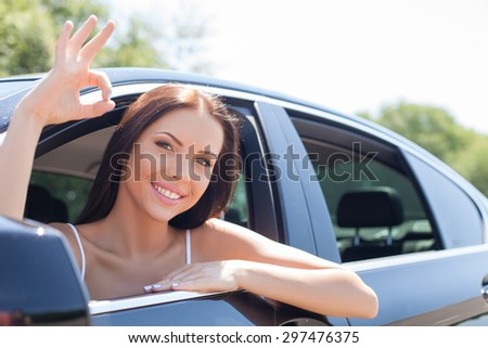 Attractive girl is sitting in a modern car. She is looking through window and showing okay sign. The lady is smiling with joy