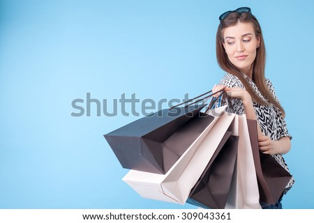 Attractive girl is standing and posing. She is carrying many packets of bought things and looking back at it happily. She is gently smiling. Isolated on blue background and copy space in left side - stock photo