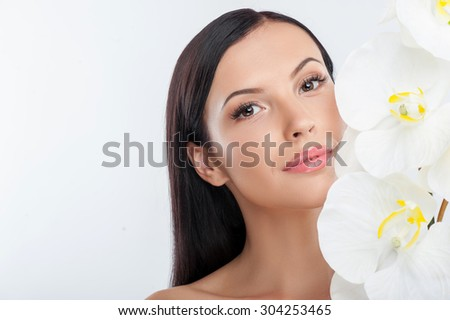 Attractive girl is touching white flowers to her cheek. She is gently smiling and looking at the camera with pleasure. Isolated on background and copy space in left side