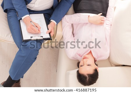 Attractive girl is visiting a psychologist - stock photo