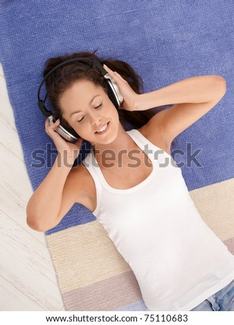 Attractive girl laying on floor at home, listening to music through headphones, smiling, eyes closed.? - stock photo