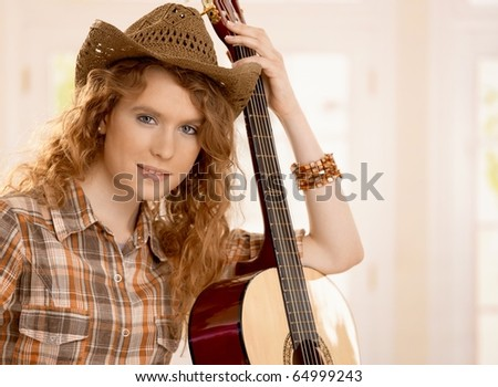 Attractive girl leaning on guitar, dressed in country style.? - stock photo