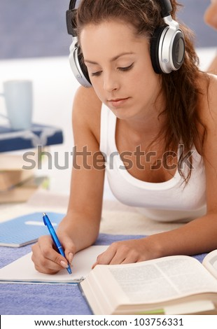 Attractive girl learning at home laying on floor, using headphones. - stock photo
