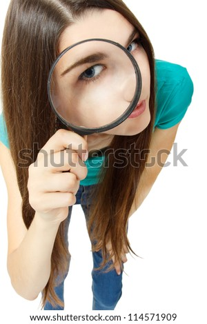 Attractive girl looking through a magnifying glass over white background - stock photo