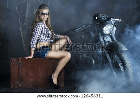 Attractive girl next to the old german motorcycle studio installation - stock photo