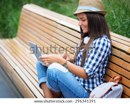 Attractive girl on a bench with a laptop - stock photo