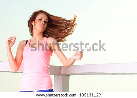 Attractive girl on pier wind in hair Young woman on background of sea sky