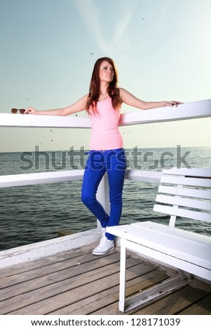 Attractive girl on pier Young woman on background of sea full length